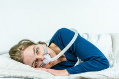 CPAP, sleep apnea treatment.Woman laying on her side with eyes open Stock Images