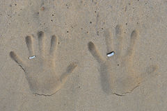 Cópias da mão com alianças de casamento na areia da praia Fotos de Stock Royalty Free