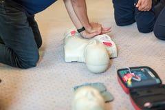 CPR训练使用和在一个成人训练人体模型的一个AED和袋子面具阀门 免版税库存照片