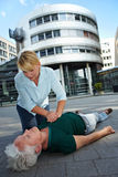 CPR as First Aid. Passerby giving CPR to senior women as First Aid Stock Photo