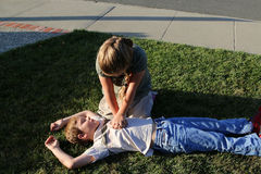 CPR Compression. Young girl gives life saving compressions to an young boy in cardiac arrest stock photos
