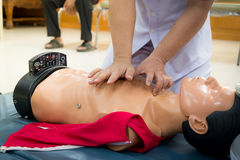 CPR First Aid Training Concept. CPR training medical procedure - Demonstrating chest compressions on CPR doll in the class royalty free stock photography