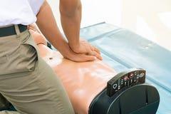 CPR-hulp proef medische opleiding met sluiten-omhoog het Hart van de handpers op de verfrissing van de poppennoodsituatie opleidi royalty-vrije stock afbeeldingen