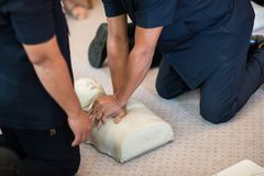 CPR training using and an AED and bag mask valve on an adult training manikin. royalty free stock photography