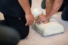 CPR training using and an AED and bag mask valve on an adult training manikin. royalty free stock images