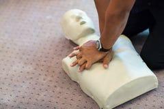 Cpr-Trainingsanwendung und ein AED- und Taschenmaskenventil auf einem erwachsenen Trainingsmännchen Lizenzfreies Stockbild