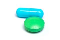 Cápsula azul y píldora verde Imágenes de archivo libres de regalías