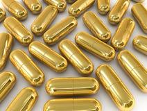 Cápsula de la píldora del oro Fotografía de archivo libre de regalías
