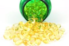 Cápsulas de la vitamina D-3 con la botella de píldora verde Fotos de archivo