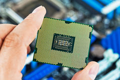 CPU in hand. Macro view of modern multicore CPU processor in human hand with PC computer motherboard in background. Selective focus DOF effect stock photo