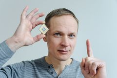 CPU in the man`s hand. A man is holding a processor near his head Stock Photo
