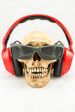 Cráneo con el auricular y las gafas de sol rojos en el fondo blanco Foto de archivo libre de regalías