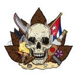 Cráneo con el cigarro en el fondo de las hojas del tabaco, un machete y una bandera cubana, colocándose en la arena Foto de archivo libre de regalías