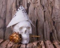 Cráneo con el sombrero del periódico y de los cardos en sus dientes Imagenes de archivo