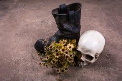 Cráneo con la bota y la flor Imágenes de archivo libres de regalías