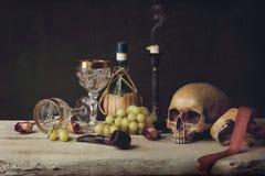 Cráneo de la bruja de Vanitas; Tubo, tabaco, copa de vino, vino y uva Imagen de archivo libre de regalías