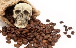 Cráneo en el saco de carne asada del grano de café en el fondo blanco Foto de archivo