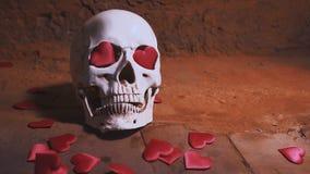 Cráneo humano con el corazón rojo Caída de los corazones en la cámara lenta del cráneo Concepto para el día del ` s de la tarjeta metrajes