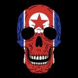 Cráneo humano con la bandera norcoreana aislada en fondo negro fotos de archivo