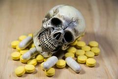 Cráneo humano en la pila de drogas, de enfermedad y de peligro Imagen de archivo libre de regalías
