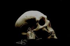 Cráneo humano y un reloj Imágenes de archivo libres de regalías