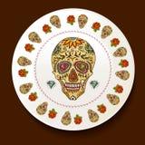 Cráneo y flores en una placa blanca Imagenes de archivo