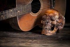 Cráneo y guitarra en la madera, Fotos de archivo libres de regalías