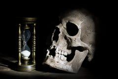 Cráneo y reloj de arena del vintage en fondo de madera bajo haz de luz Fotografía de archivo