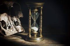 Cráneo y reloj de arena del vintage en fondo de madera bajo haz de luz Foto de archivo