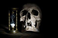 Cráneo y reloj de arena del vintage en fondo de madera bajo haz de luz Fotografía de archivo libre de regalías