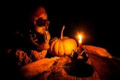 Cráneo y vela con la palmatoria en de madera Foto de archivo
