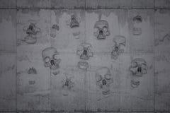 Cráneos en una pared del hormigón ilustración del vector