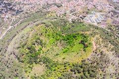 Cráter antiguo extinto de un volcán cubierto con el bosque cerca de la ciudad, visión aérea imagen de archivo libre de regalías