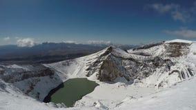 Cráteres sitiados por la nieve y un lago del cráter del volcán activo de Gorely en la península de Kamchatka almacen de video