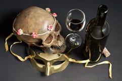 Crâne avec le masque et le vin image stock
