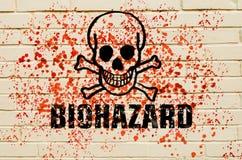 Crâne de risque biologique sur le mur avec les pulvérisateurs toxiques rouges sur le mur Photo stock