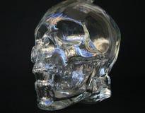 Crâne en verre avec l'au sol de dos de noir Photographie stock