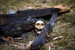 Crâne humain parmi les charbons dans les cendres du feu photos stock