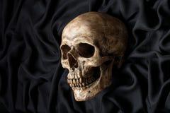 Crâne sur le tissu noir Photos libres de droits