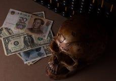 Crâne sur le vieux bois avec des yuans de billet de banque et dollar dans la vie immobile Photo stock