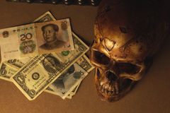 Crâne sur le vieux bois avec des yuans de billet de banque et dollar dans la vie immobile Images stock