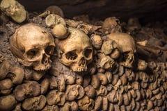 Crânes et os dans des catacombes de Paris Photographie stock libre de droits