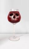 Crânio alcoólico no vidro com vinho tinto Imagens de Stock Royalty Free