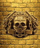 Crânio, armas douradas e corrente em um fundo do tijolo dourado wal Fotografia de Stock