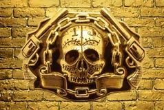 Crânio, armas douradas e corrente em um fundo do tijolo dourado wal Foto de Stock Royalty Free