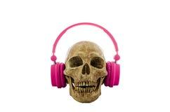 Crânio com os fones de ouvido cor-de-rosa isolados no fundo branco imagens de stock