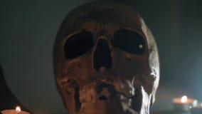 Crânio com os olhos roxos cobertos no fumo branco A mão coloca as velas em torno do crânio humano Halloween filme