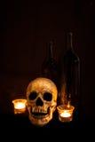 Crânio e vinho do vintage pela luz de vela Foto de Stock