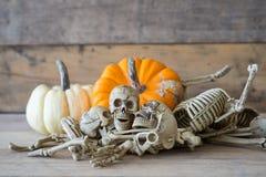 Crânio humano no fundo, no esqueleto e na abóbora de madeira na madeira, fundo feliz de Dia das Bruxas Imagens de Stock Royalty Free
