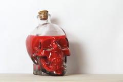 Crânio humano que contém o sangue ou o veneno fotografia de stock royalty free